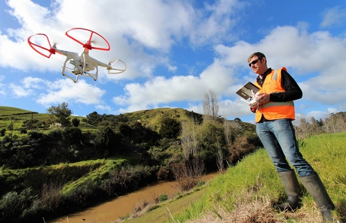 Man operating a drone to survey river works.