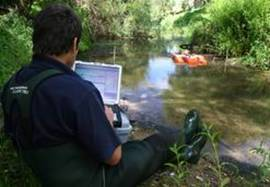 Using ADCP and laptop to measure water flow.