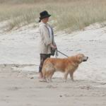 Person on the beach with a dog.