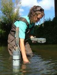 An NRC staff member taking water samples in a river.