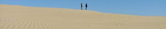 People standing on a sand dune.